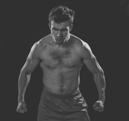 Portrait of strong muscular sports man with an intense furious look. Expressive sexy shirtless angry man looking powerful on black background in Workout, training and fitness concept.