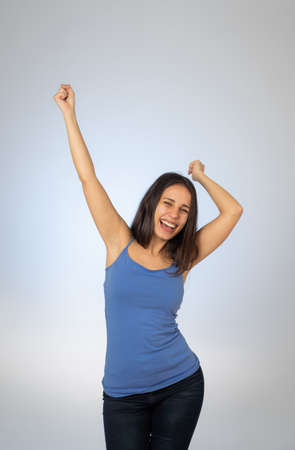 Portrait of young attractive woman celebrating success winning or feeling lucky and joyful dancing and making celebration gestures with arms isolated on blue background In People Human emotions.