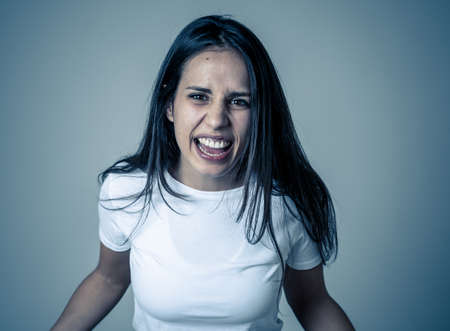 Close up of young attractive frustrated latin woman in stress with furious face. Looking mad and disappointed making angry gestures. In neutral background. In human facial expressions and emotions.