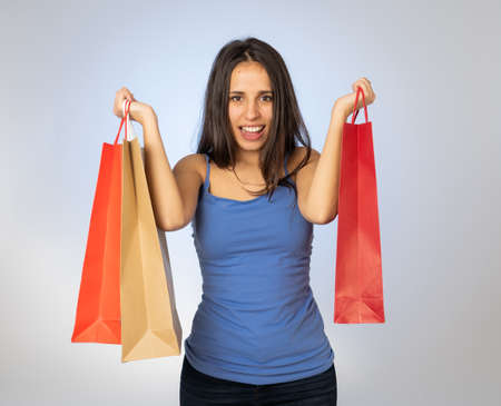 Happy latin young woman holding colorful bags happy and cheerful after a shopping day. Excited teenager with paper bags buying in new season sales. In fashion and and shopping addiction concept 免版税图像 - 152493783
