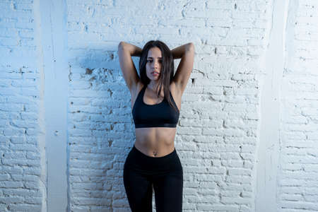 Beauty portrait of sport woman wearing gym suit looking sensual and fit. Studio shot of latin sexy strong woman in sportswear looking healthy posing against brick wall. In fitness Body care concept. 免版税图像 - 152493788