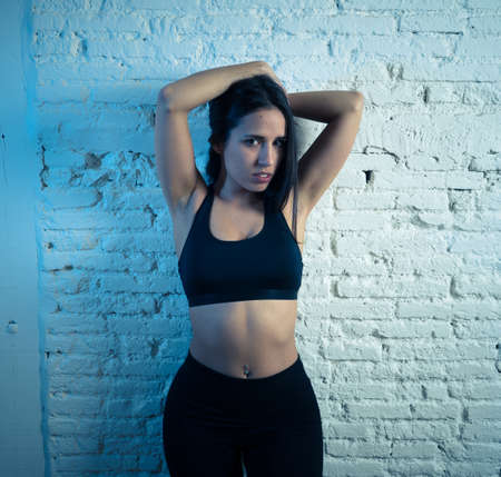 Beauty portrait of sport woman wearing gym suit looking sensual and fit. Studio shot of latin sexy strong woman in sportswear looking healthy posing against brick wall. In fitness Body care concept.