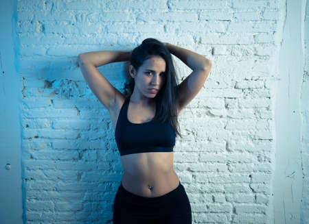 Beauty portrait of sport woman wearing gym suit looking sensual and fit. Studio shot of latin strong woman in sportswear looking healthy posing against brick wall. In fitness Body care concept.
