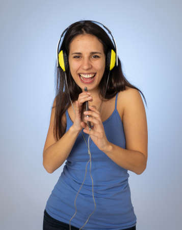 Portrait of gorgeous and happy brunette latin woman listening to music on mobile smartphone with headphones singing and dancing on neutral background. In Technology youth and happiness concept. Stock fotó
