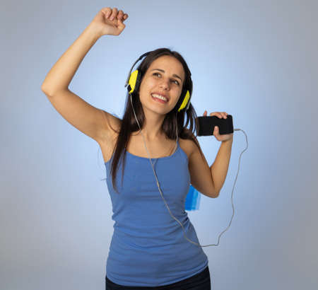 Portrait of gorgeous and happy brunette latin woman listening to music on mobile smartphone with headphones singing and dancing on neutral background. In Technology youth and happiness concept. 免版税图像 - 152493842