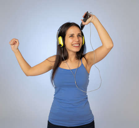 Portrait of gorgeous and happy brunette latin woman listening to music on mobile smartphone with headphones singing and dancing on neutral background. In Technology youth and happiness concept. 免版税图像 - 152493844