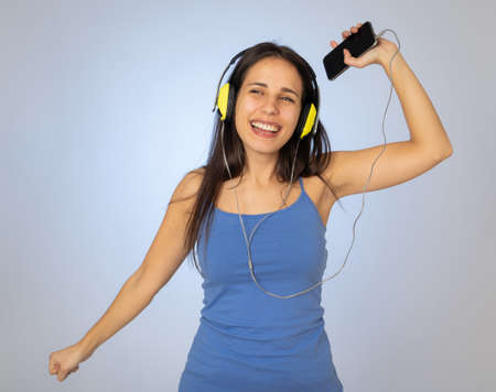 Portrait of gorgeous and happy brunette latin woman listening to music on mobile smartphone with headphones singing and dancing on neutral background. In Technology youth and happiness concept. 免版税图像