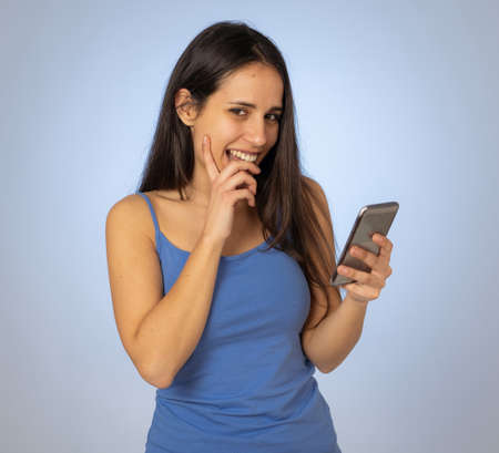 Young latin woman on mobile looking happily shocked at social media app dating site. Teenager girl having lots of followers and likes on online video blog In millennial generation using technology. 免版税图像