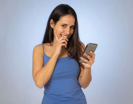 Young latin woman on mobile looking happily shocked at social media app dating site. Teenager girl having lots of followers and likes on online video blog In millennial generation using technology. Stock fotó