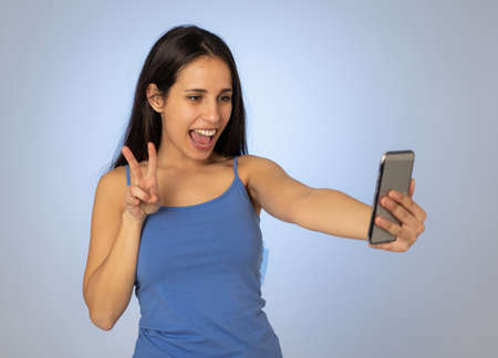 Studio shot of Young cool pretty latin teenager woman taking selfie with mobile smart phone having fun and looking beautiful sexy In millennial generation using mobile and social media addiction. Stock fotó - 152493867