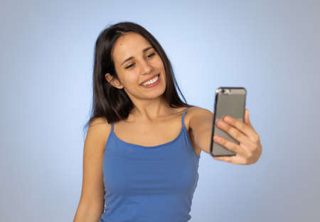 Studio shot of Young cool pretty latin teenager woman taking selfie with mobile smart phone having fun and looking beautiful sexy In millennial generation using mobile and social media addiction.
