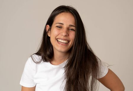 Close up portrait of attractive brunette young latin woman with happy face beautiful smile and long black hair. Isolated on neutral background. In People, positive human facial expressions and emotions.