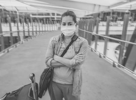 Coronavirus outbreak travel ban and restrictions. Traveler man with face mask at international airport affected by flight cancellation. COVID-19 pandemic and worldwide borders closures and shutdowns.