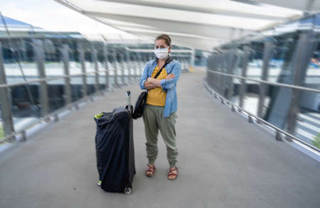 Coronavirus outbreak travel ban and restrictions. Traveler man with face mask at international airport affected by flight cancellation. COVID-19 pandemic and worldwide borders closures and shutdowns. Фото со стока