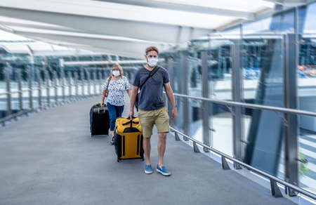 Coronavirus outbreak travel ban and restrictions. Traveler man with face mask at international airport affected by flight cancellation. COVID-19 pandemic and worldwide borders closures and shutdowns. Foto de archivo