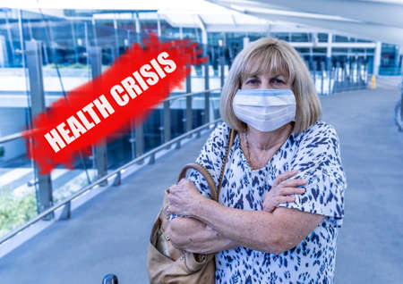 COVID-19 Pandemic. Senior traveler with face mask airport affected by flight cancellation and border restrictions with word health crisis written in red. Coronavirus Outbreak impact concept.