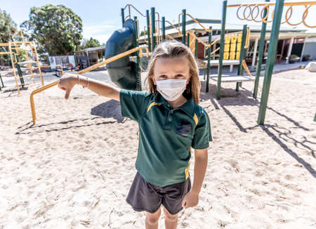 Covid-19 outbreak schools closures. Sad Schoolgirl with face mask bored feeling depressed and lonely in empty playground as school is closed. Restrictions and lockdown as Coronavirus containment measures.