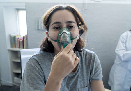 Young attractive woman with oxygen mask looking sad and worried at hospital bed in clinic bedroom in lung cancer diagnose, smoking and respiratory disease and anti tobacco advertising campaign. Standard-Bild