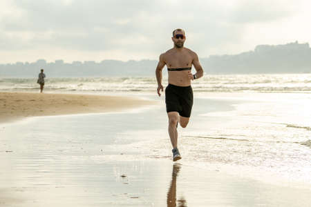 Sports fitness man with heart rate monitor running on beach with smart watch. Fit body male runner doing jogging workout at the sea in sport exercise and technology and healthy lifestyle concept. Foto de archivo