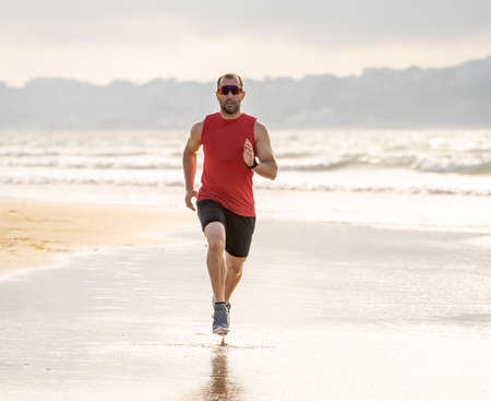 Athlete runner man running, sprinting and training in sport wear on beach at sunset. Fitness model male training and working outdoors on sea shore in Sports and Active healthy lifestyle.
