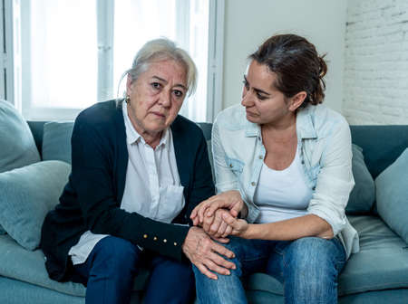 Depressed senior mother and daughter embracing each other grieving loss of loved ones amid Coronavirus pandemic. Two sad women at home in lockdown in People and families affected by COVID-19 outbreak.