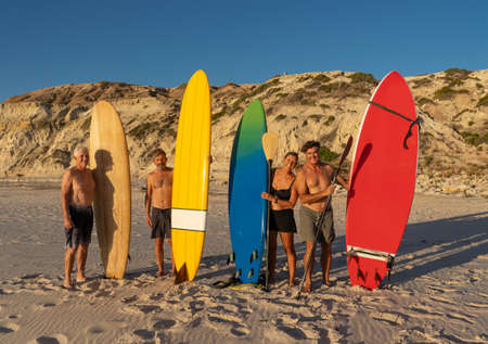 Group of senior surfers, woman and men, holding their colorful surfboards on remote beach. Mature retired friends enjoying surfing and outdoors lifestyle in Healthy people and aging in modern world.