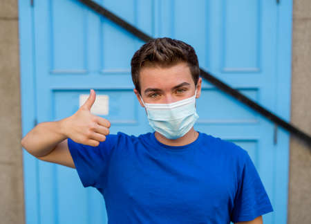 Young man wearing medical protective surgical face mask against infectious Coronavirus disease. Conceptual portrait of New Normal and Protection against Covid-19 outbreak.