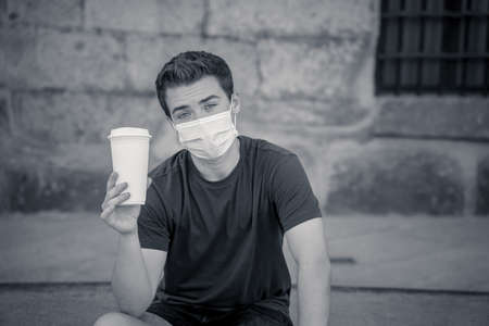 COVID-19 outbreak. Young man walking in city street wearing protective surgical face mask and drinking coffee. Coronavirus, the New Normal and mandatory use of face mask