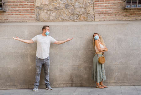 Man and woman wearing face mask standing 6 feet from each other keeping social distancing avoiding physical contact, infection and the spread of coronavirus. COVID-19 health protocols and New Normal.