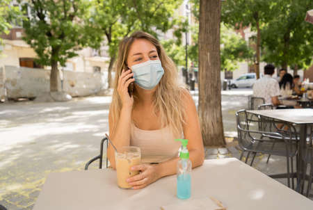 Young woman with protective mask and hand sanitizer on video call using mobile phone in coffee shop in city street. COVID-19 and New Normal, Health safety protocols as mandatory use of face mask. 免版税图像