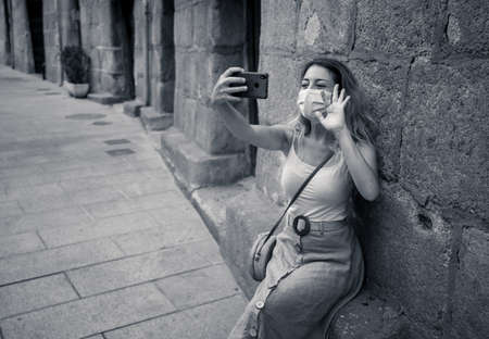 Young woman in city street wearing protective face mask and using mobile phone video calling or on video conference. The New Normal, technology and use of face mask to protect against coronavirus.