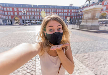 Beautiful young caucasian tourist woman wearing protective face mask happy in Plaza Mayor Madrid taking a selfie, sending a virtual kiss and showing thumbs up. COVID-19 and travel in the New Normal.