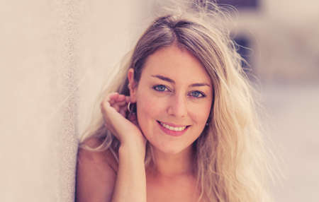 Outdoors close up portrait of young attractive woman with beautiful blonde hair and sensual smile. Female model posing with natural beauty and light. Real People, beauty care, fashion and lifestyle. 免版税图像