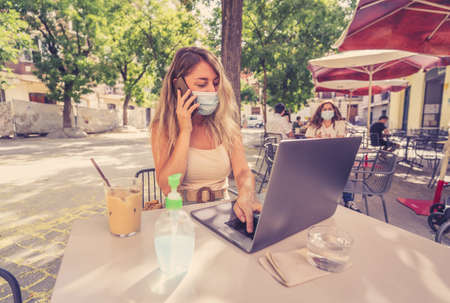 Young woman wearing protective face mask and using hand sanitizer while working remotely on computer laptop in coffee shop outdoors. The New Normal and government health regulations against COVID-19.