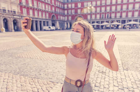 Beautiful young caucasian woman wearing protective face mask happy and excited in Plaza Mayor Madrid taking a selfie. In COVID-19 and the New Normal lifestyle, tourism, and travel in Europe.