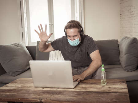 Happy business man on laptop working from home. Freelancer on computer on a video conference with employees working remotely in coronavirus Lockdown, Social Distancing and New Normal concept. 免版税图像