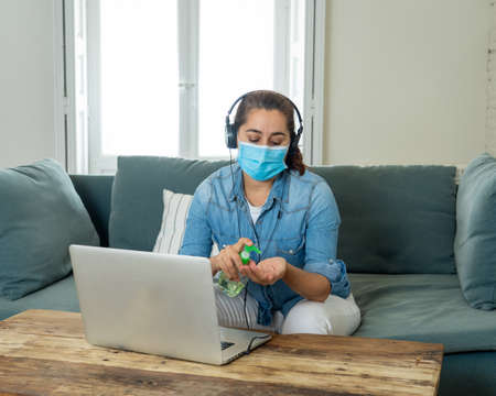 Happy successful woman on laptop working from home. Freelancer or employee in video conference virtual meeting working remotely in COVID-19 lockdown, social distancing and New normal concept. 免版税图像