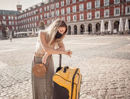 Worried Woman tourist with face mask and luggage stressed amid self-isolation travel requirements. Tourist affected by new travel regulations. Covid-19 and international tourism. Stok Fotoğraf