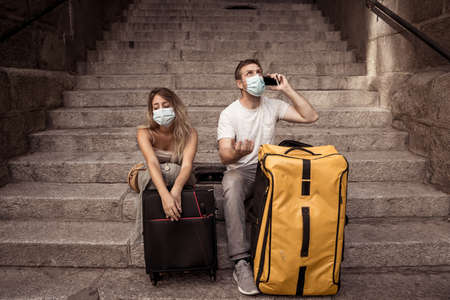 Worried Woman and man tourists with face mask and luggage on mobile distressed amid self-isolation travel requirements. Tourist affected by new travel regulations. Covid-19 and international tourism. Stok Fotoğraf