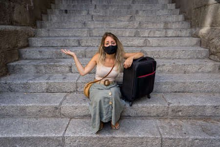 Worried tourist woman with luggage wearing protective face mask distressed amid self-isolation travel requirements. Tourist affected by new travel regulations. Covid-19 and international tourism. Stok Fotoğraf