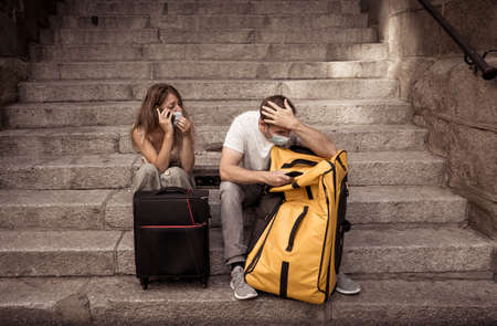 Worried Woman and man tourists with face mask and luggage on mobile distressed amid self-isolation travel requirements. Tourist affected by new travel regulations. Covid-19 and international tourism. 免版税图像