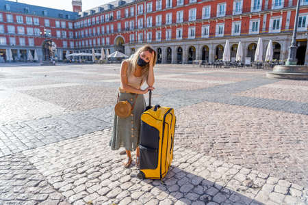Worried Woman tourist with face mask and luggage stressed amid self-isolation travel requirements. Tourist affected by new travel regulations. Covid-19 and international tourism. 免版税图像