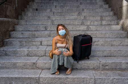 COVID-19 impact in international tourism. Sad tourist woman worried about coronavirus quarantine back home amid new travel regulations. Vacations cancellations due to coronavirus travel restrictions. 免版税图像