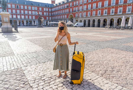 Covid-19 impact in tourism. Worried tourist in Madrid Spain wearing face mask talking on mobile distressed amid self-isolation travel requirements. Woman with luggage affected by travel regulations.