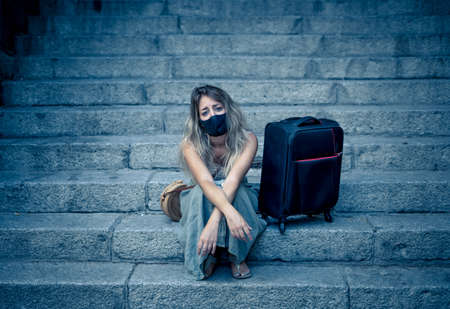 Worried tourist woman with luggage wearing protective face mask distressed amid self-isolation travel requirements. Tourist affected by new travel regulations. Covid-19 and international tourism. Banco de Imagens