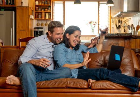 Life at home image of Happy couple video calling friends and family using laptop. Man and woman online chatting cheering with wine in virtual celebration party of easing of coronavirus restrictions.