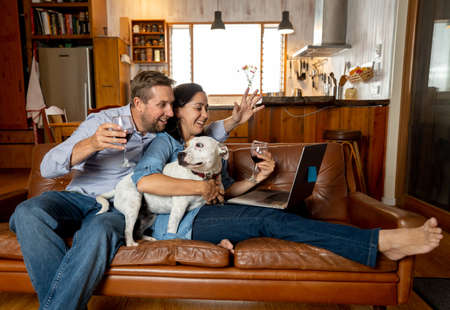 Happy couple and pet dog video calling friends using laptop. Man and woman online chatting celebrating easing of coronavirus restrictions. Hope and positive images of Life at Home and New Normal.