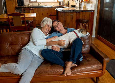 Confident couple girlfriends relaxing and loving their cute pet dog enjoying life at home together. Positive image of coronavirus Outbreak Stay Safe and animal benefits for mental health Concept. Stok Fotoğraf