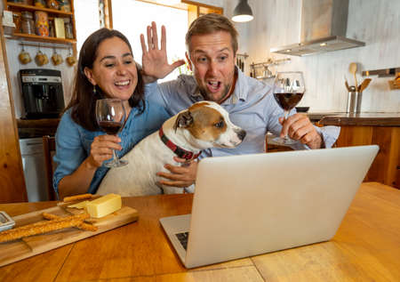 COVID-19 Stay safe Stay connected. Happy young couple video calling friends using laptop. man and woman with pet dog online chatting with family during coronavirus lockdown and social distancing.