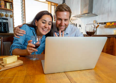 COVID-19 Stay safe Stay connected. Happy young couple video calling friends using laptop at home. Man and woman online chatting with family during coronavirus lockdown and social distancing. 免版税图像